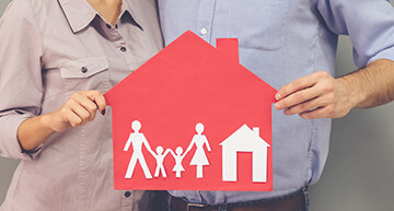 Couple holding a house graphic with kids - Home Insurance