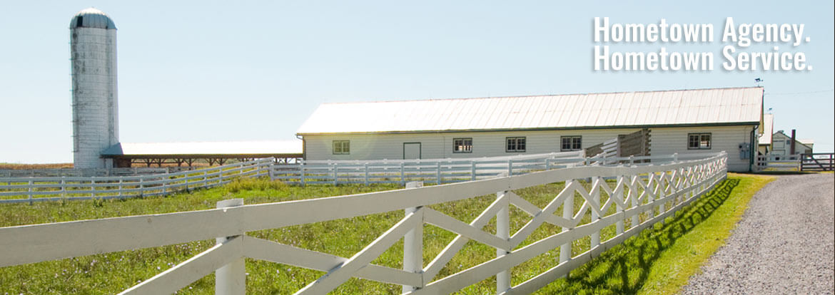 White fence leading up to farm buildings - Farm Insurance